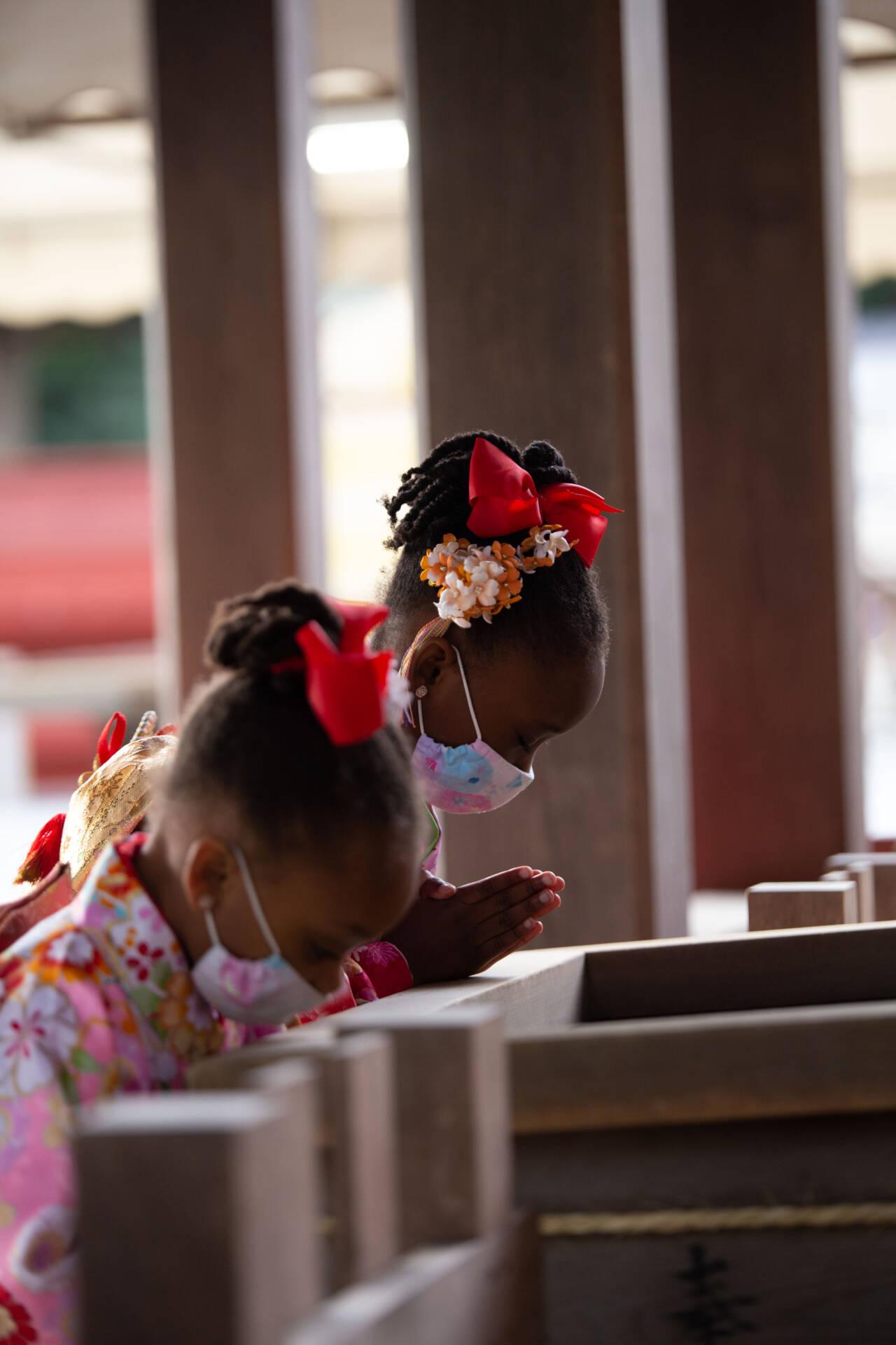 Masked girls praying at Japanese shrine.